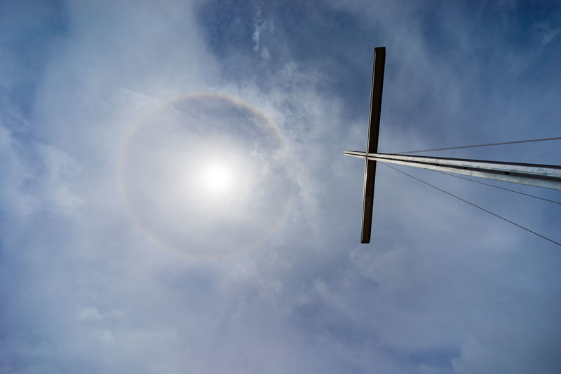 Sun halo over Prayer Mountain at Bario, Sarawak. The ring is caused by sunlight passing through ice crystals in cirrus clouds within the Earth's atmosphere. BARIO Borneo Cross Faith Sun Halo Astronomy Cloud - Sky Day Low Angle View Malaysia Nature No People Outdoors Sarawak Sky Vapor Trail