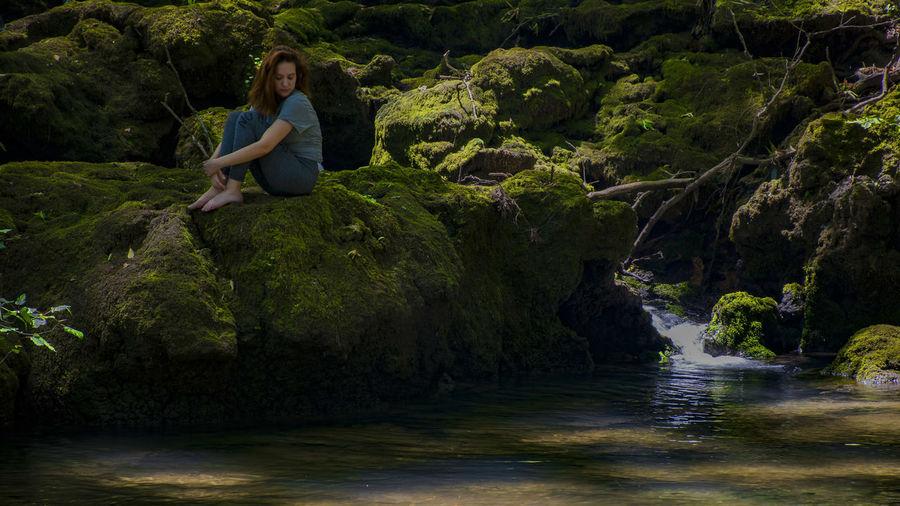 Woman sitting on rock by stream