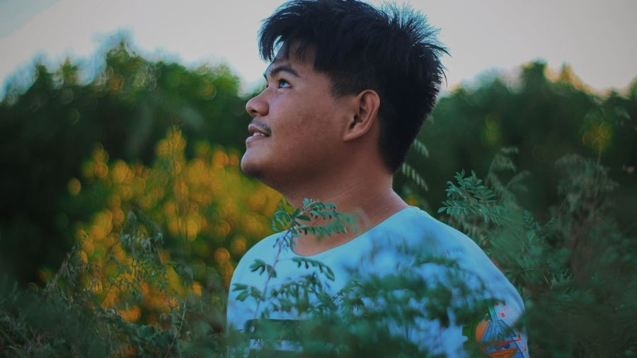 Portrait of young man looking away against plants