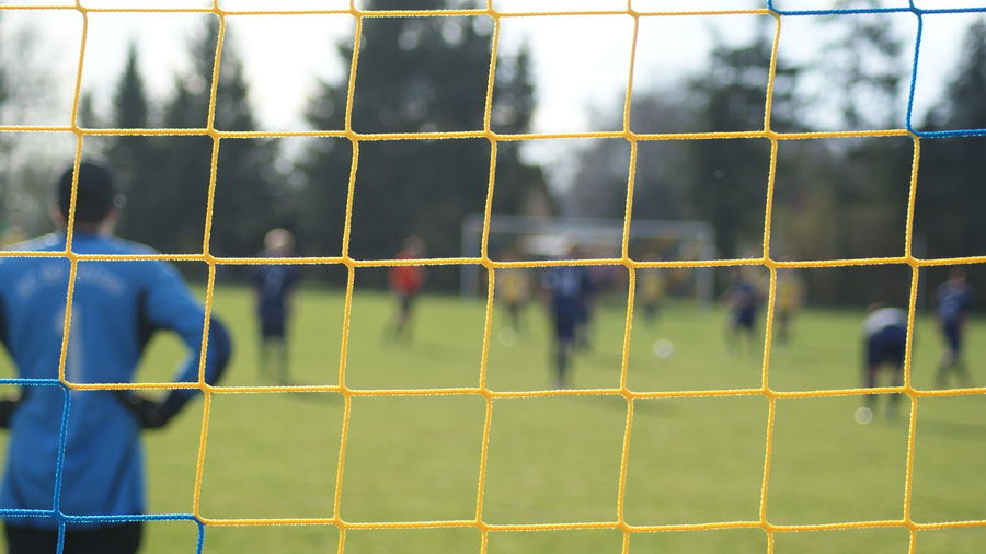 Players on soccer field seen through net