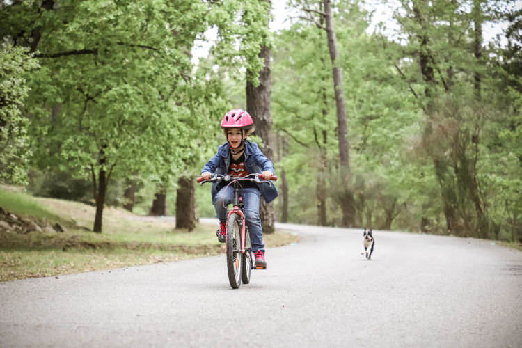 Girl riding bicycle while dog running on road in forest