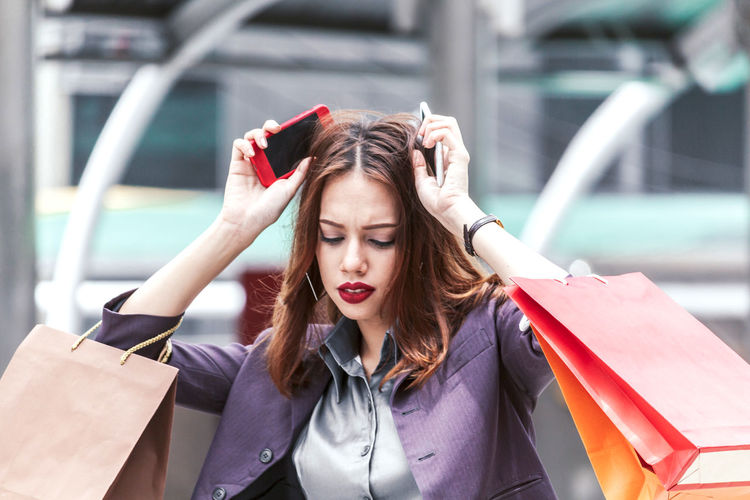 Thoughtful young woman with mobile phones and shopping bags on walkway