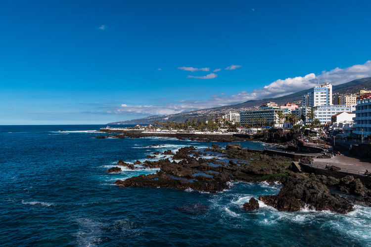 PUERTO DE LA CRUZ, TENERIFE / SPAIN - FEBRUARY 24 2018: View on bay of Puerto de la Cruz in the morning Architecture Beach Blue Building Exterior Built Structure City Cloud - Sky Day Horizon Over Water Land Nature No People Outdoors Rock Rock - Object Scenics - Nature Sea Sky Solid Water Waterfront