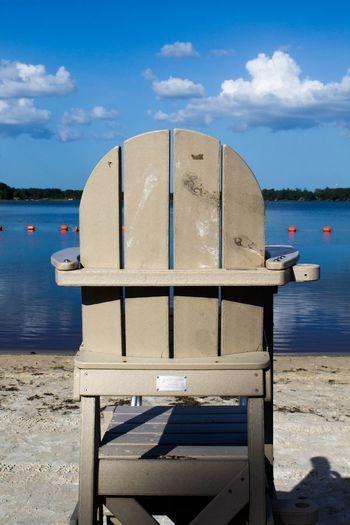 Lifeguard chair on sand at beach against sky