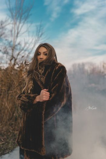 Woman standing in snow against sky during winter