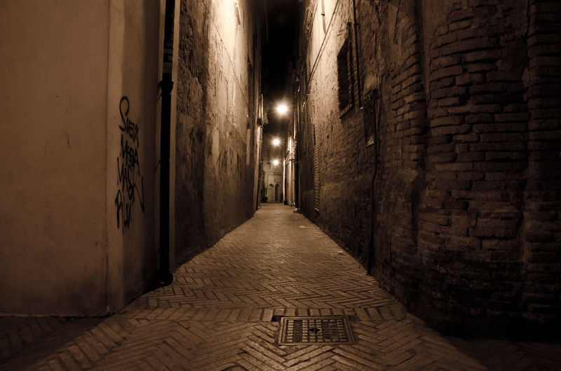 Empty narrow alley along buildings