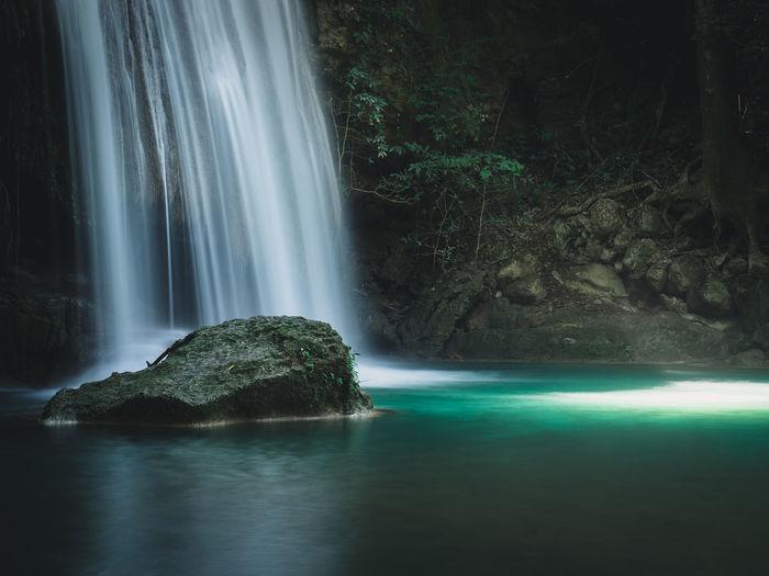 Stunning waterfall smooth stream, sunbeam and turquoise pond. erawan falls, kanchanaburi, thailand.