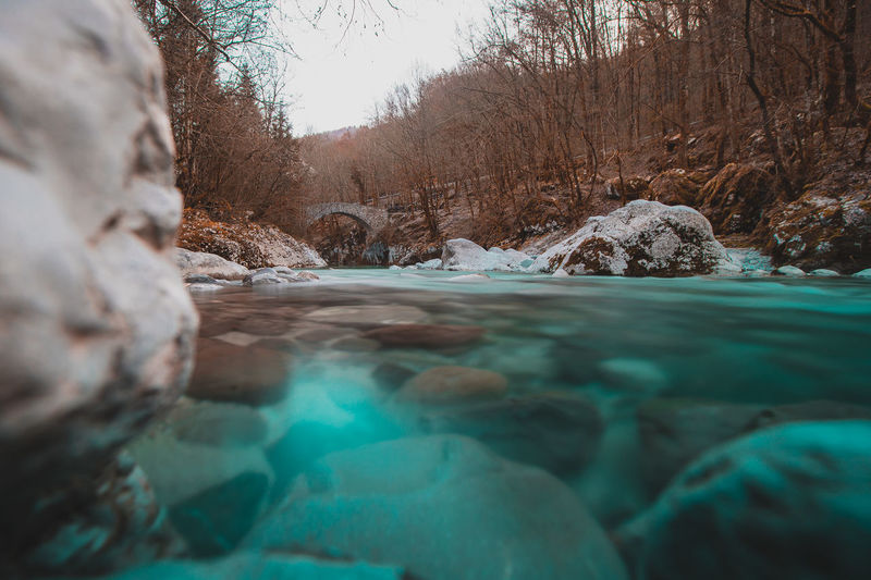 Surface level of river flowing through rocks during winter
