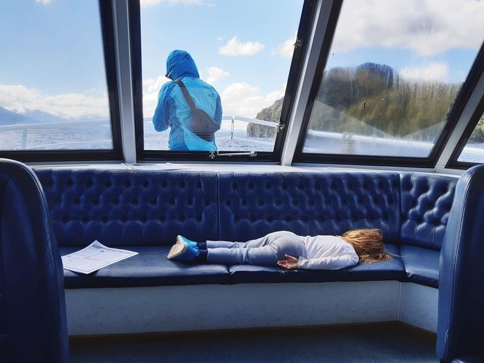 Full length of girl sleeping on seat while mother standing on deck against sky