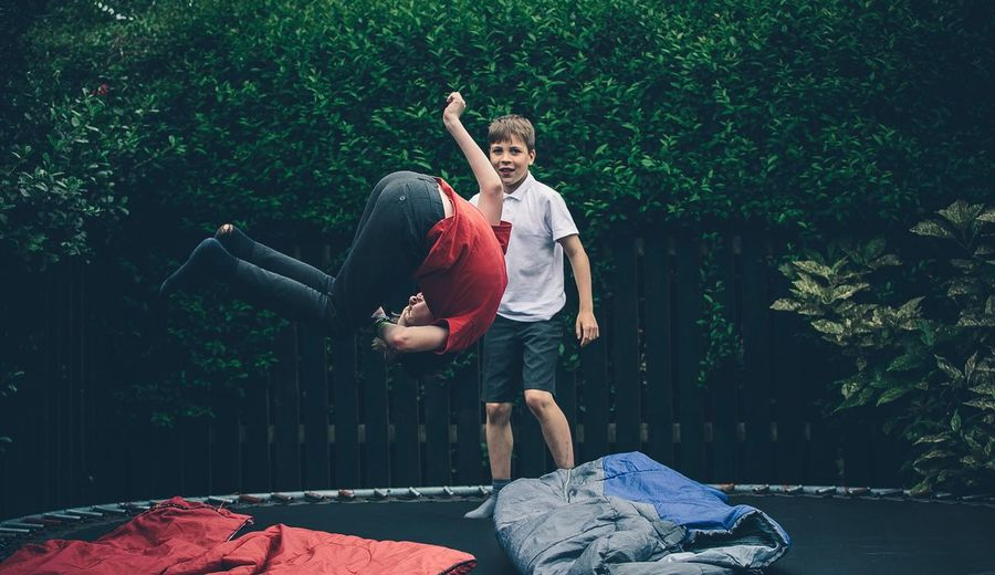 EyeEm Selects EyeEm Selects Jump School's Out Jumping Boys Child Vitality Fun Males  Happiness Outdoors Human Body Part Smiling Day Children Only Tree Trampoline Full Length Canon Outside Playing Playing Games Hedge