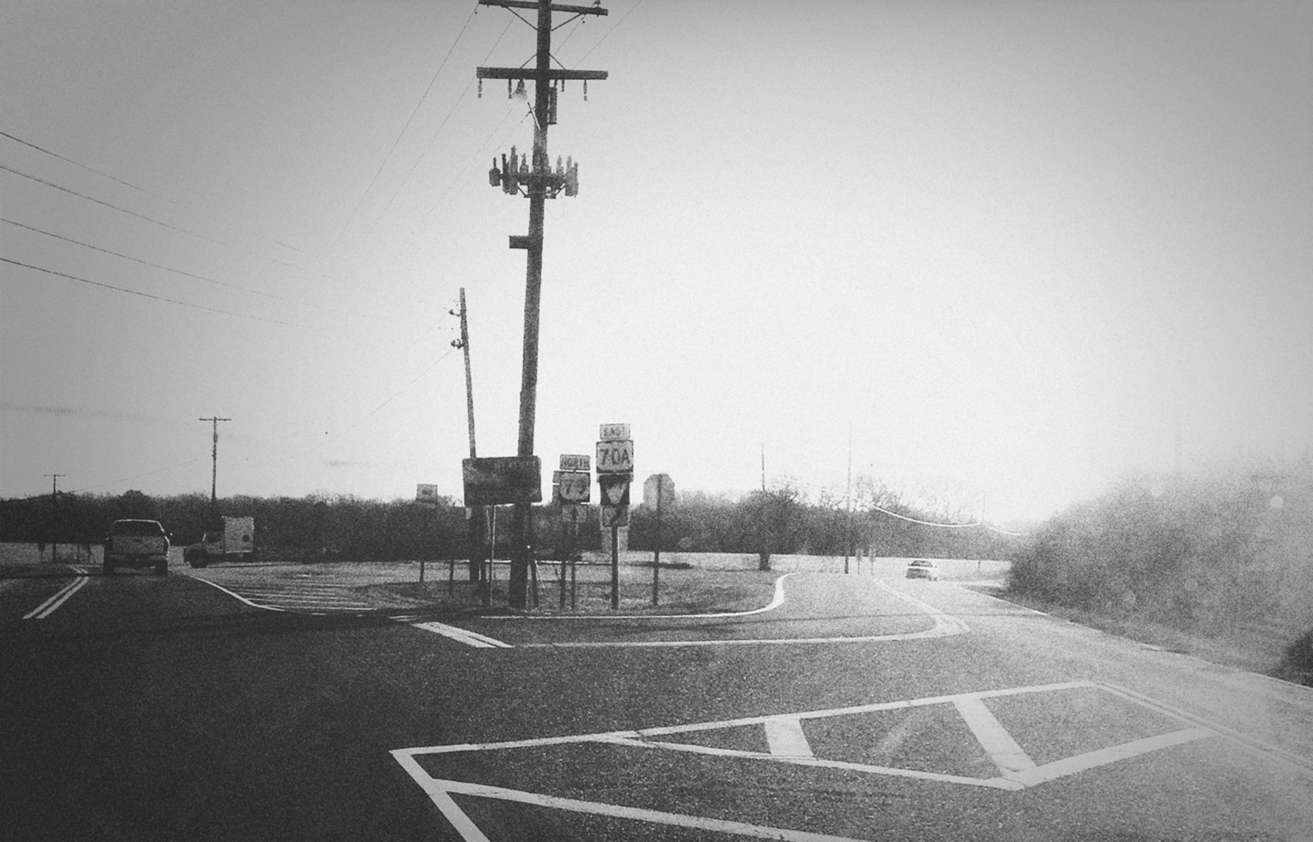 transportation, clear sky, road, mode of transport, street, the way forward, street light, car, copy space, road marking, land vehicle, day, electricity pylon, outdoors, sky, empty, no people, asphalt, power line, vanishing point