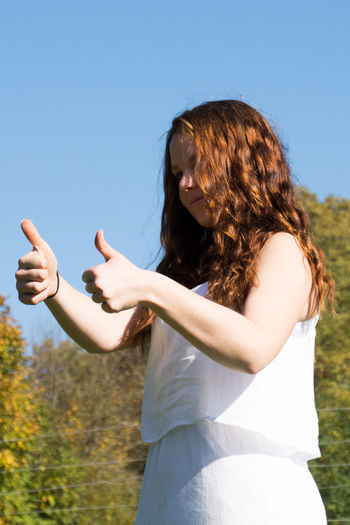 Low angle view of young woman showing thumbs up while standing against clear blue sky during sunny day