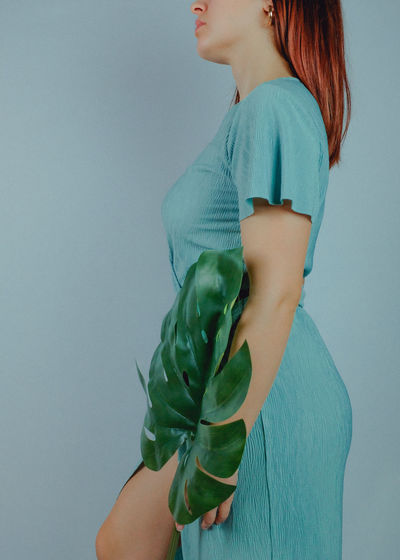 Midsection of woman holding leaf while standing blue background