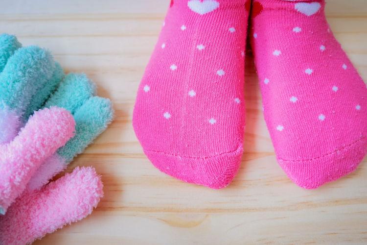 Low Section Of Woman Wearing Pink Socks On Hardwood Floor
