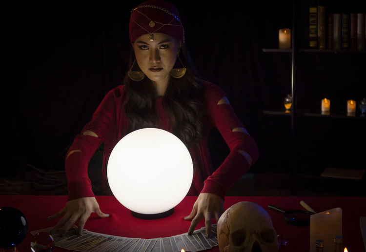 Portrait of female fortune teller with sphere at home