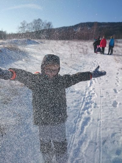 Boy with arms outstretched playing with snow on field against sky