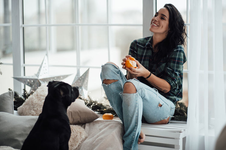 Woman with dog sitting at home