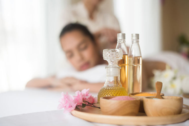 Close-up of spa product against young woman lying on massage table