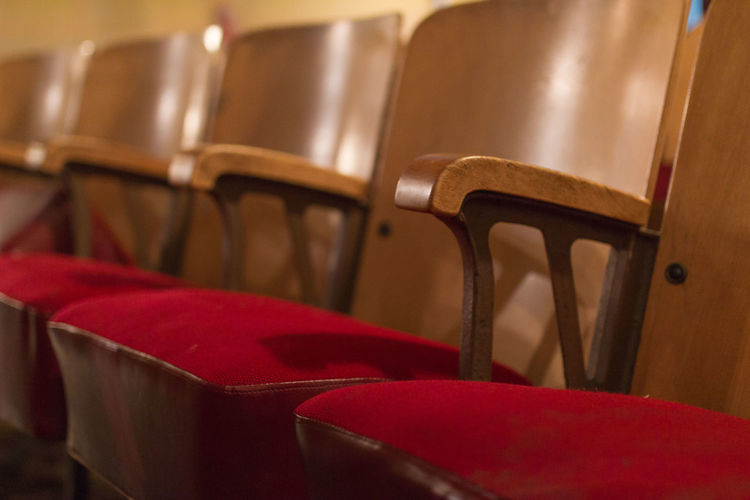 Close-up of wooden chairs at auditorium