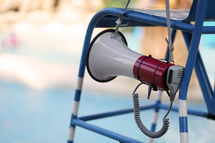 Close-up of megaphone hanging on seat outdoors