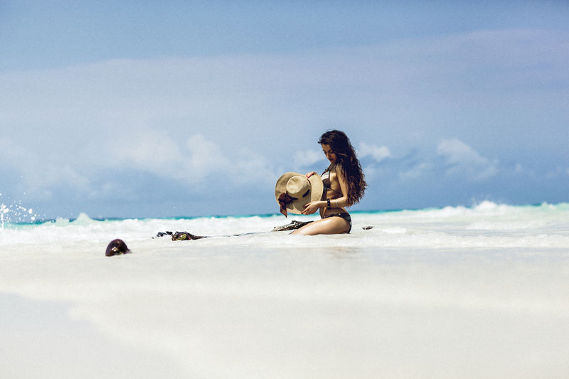 Woman relaxing on beach against sky