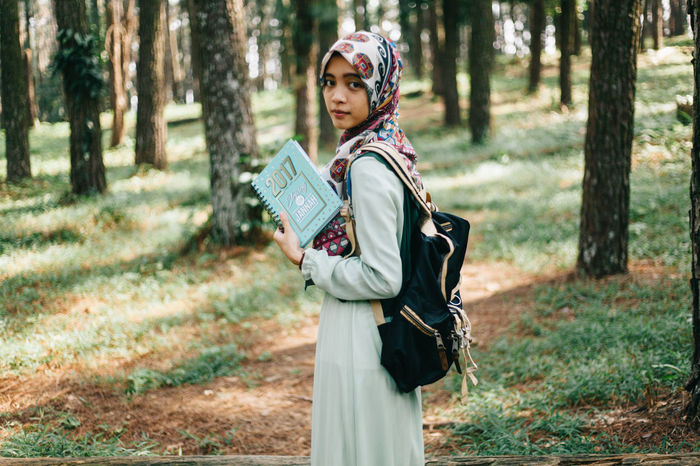 One girl is reading and holding the book on her journey. Book Books Day Daylight Forest Girl Girls Journey Journeys Outdoor Outdoors Planner Portrait Portrait Of A Woman Portraits Read Reading Reading A Book Standing Tree Trees Walk Woman Woman Portrait Women