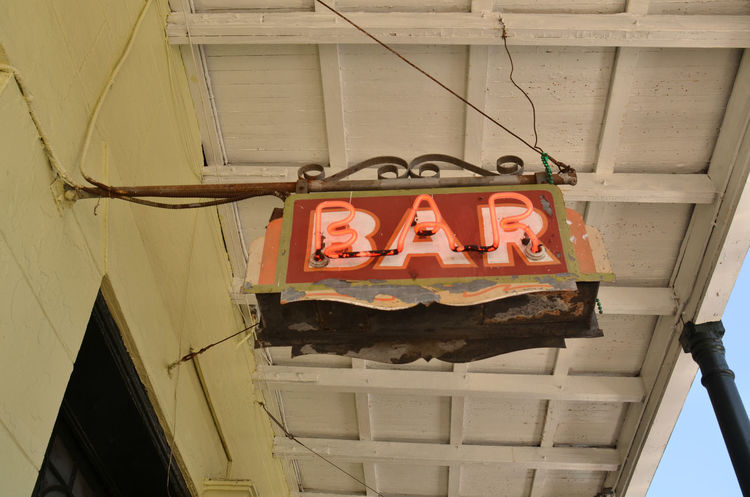 vintage bar sign hanging under covered sidewalk in French Quarter French Quarter Vintage Sign Anthropomorphic Face Architecture Bar Bar Sign Built Structure Close-up Day Low Angle View Neon Lights Neon Sign No People Outdoors