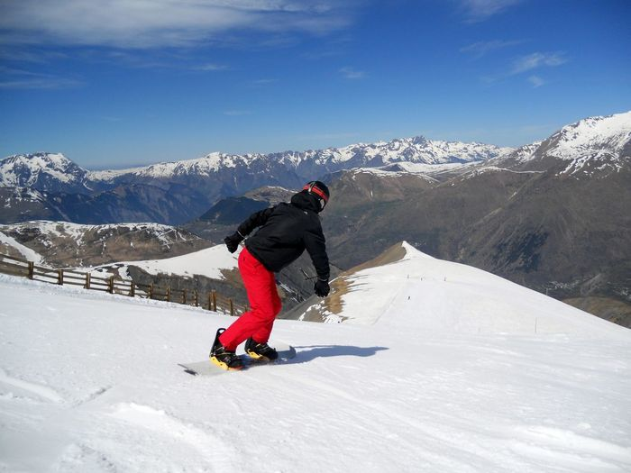 Rear View Of Young Man Snowboarding Against Sky