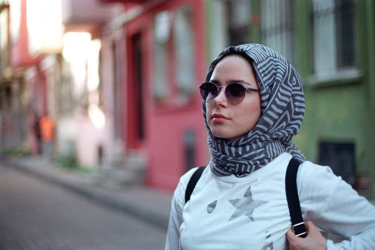Woman wearing sunglasses and scarf standing against building