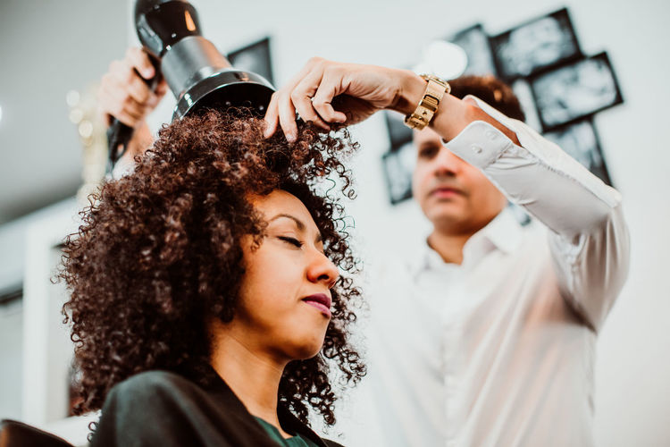 Low angle view of barber drying woman hair in salon