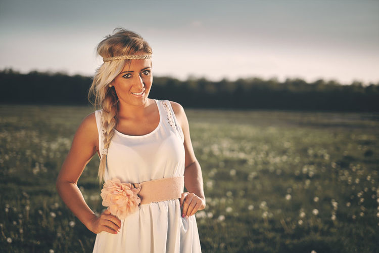 Portrait of young woman standing on grassy field during sunset