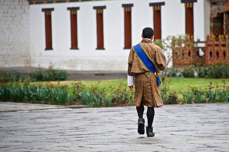 Rear view of man in traditional clothing walking on street