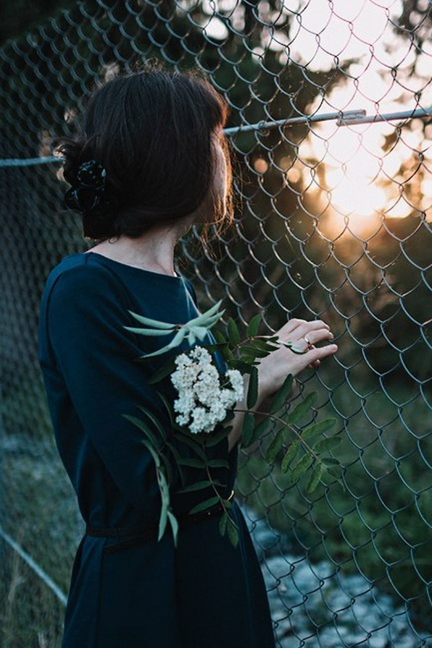 chainlink fence, one person, outdoors, hair bun, day, standing, adult, women, young adult, people, only women, one young woman only, one woman only, adults only, real people, young women, flower, freshness
