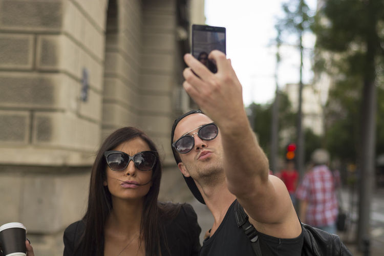 Man Taking Selfie With Friend While Standing On Road