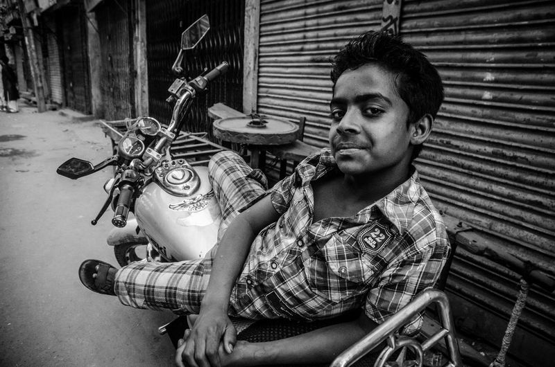 Lying on the bike, looking at the camera from the corner of his eyes. The kid was sort of born in it and it's called: Style! bangladesh, coming up on: www.vinceboisgard.com ASIA Bangladesh Blackandwhite Buy The Ticket, Take The Ride Casual Clothing Dhaka Fashion Lifestyles Motorbike Portrait Real People Streetphotography Style Texture Travel Traveling Wanderlust Youth