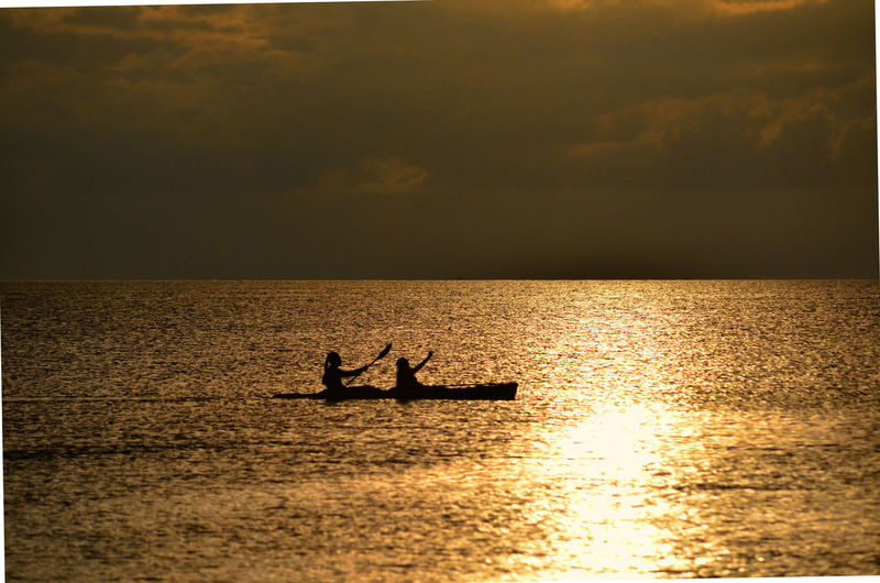 People On Canoe Boat On Sea Against Sky During Sunset