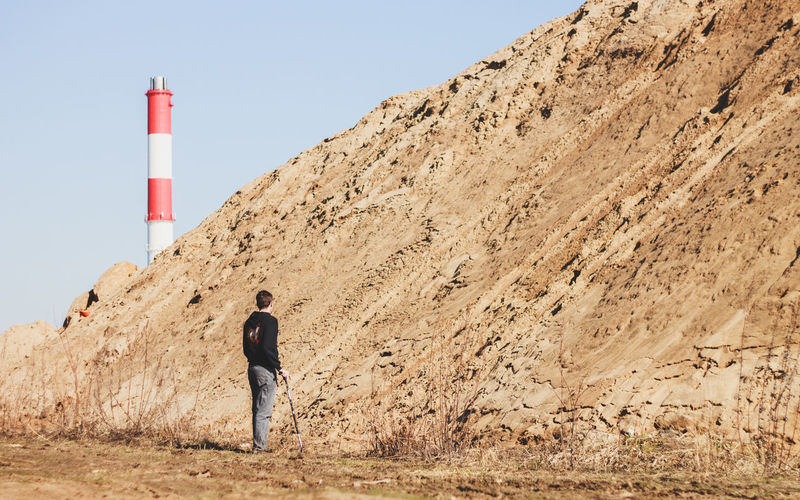 Man Standing By Heap Of Sand By Smoke Stack Against Sky