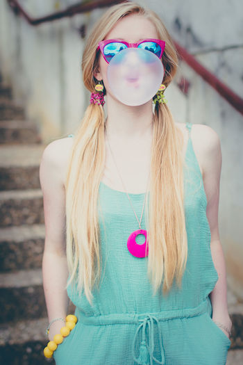 Beautiful young woman blowing up a gum like a baloon