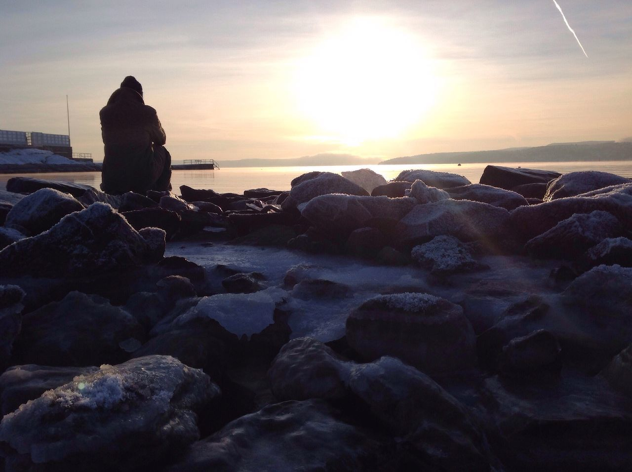 Rear View Of Woman Relaxing On Rocky Shore At Sunset