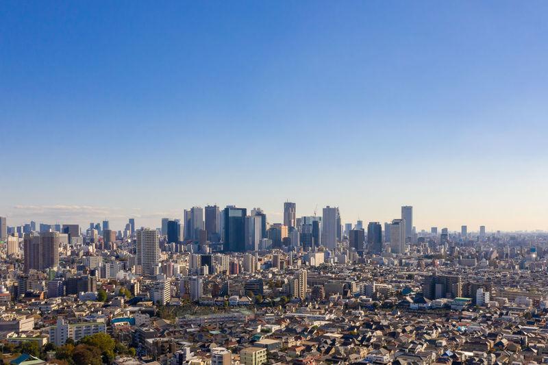 Aerial view of modern buildings in city against clear sky