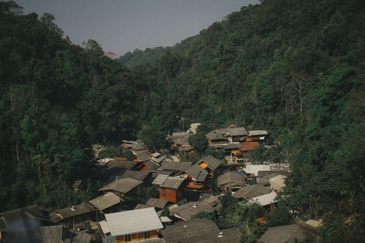 High angle view of houses and trees by mountains