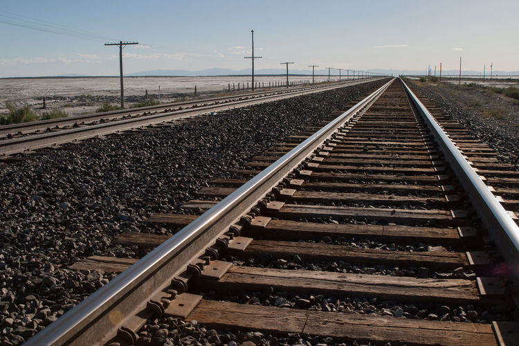 Railroad tracks by field against sky