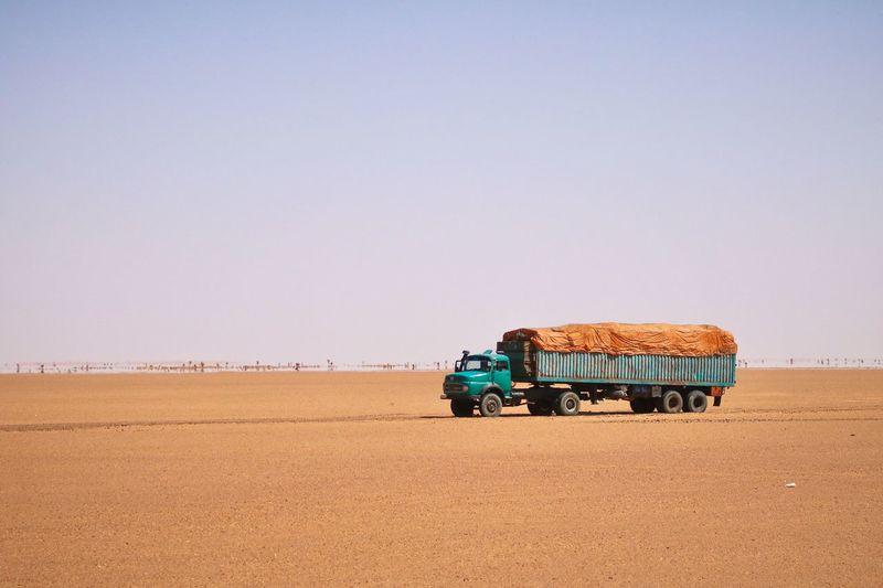 Truck on desert against clear sky