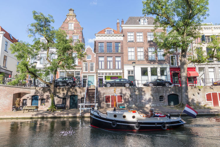 Netherlands Apartment Architecture Building Building Exterior Built Structure Canal Canal House Canal Houses City Day Holland Incidental People Mode Of Transportation Nature Nautical Vessel Oudegracht Outdoors Plant Residential District Row House Sky Transportation Tree Utrecht Water Waterfront