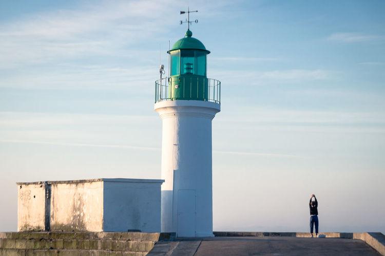 Lighthouse on building against sky