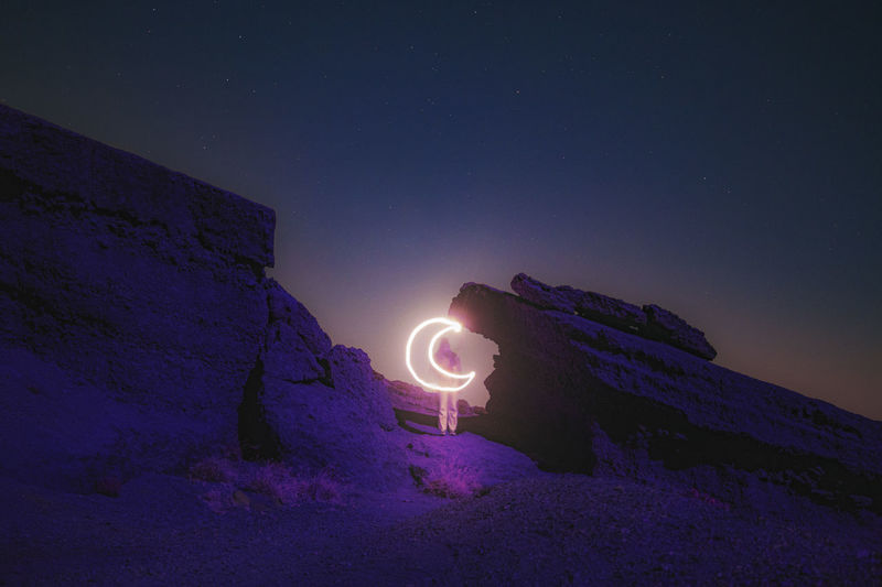 Light painting on rock against sky at night