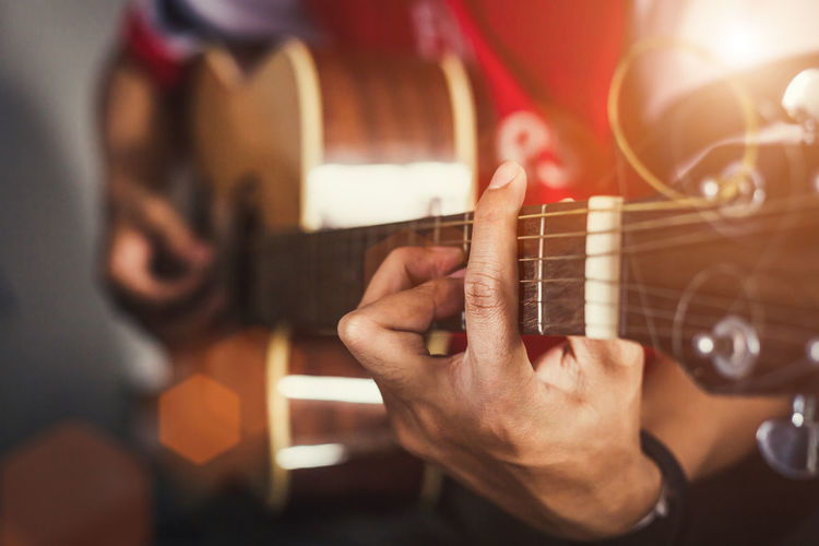 Young man playing on acoustic guitar. Acoustic Guitar Artist Finger Guitar Guitarist Hand Holding Human Hand Music Musical Equipment Musical Instrument Musician Performance Playing Skill