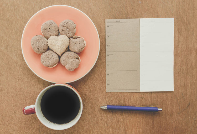 Directly Above Shot Of Black Coffee With Paper And Pen By Cookies On Table
