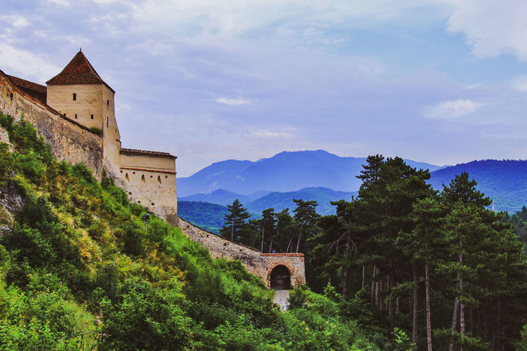 View of old castle by trees against mountains and sky