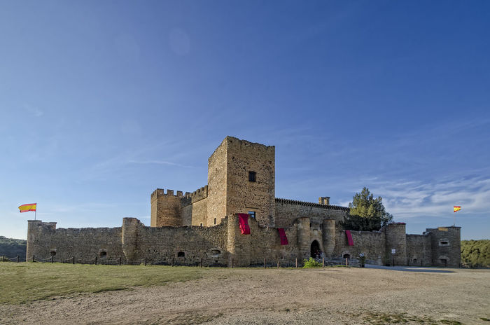 Castillo de Pedraza (Segovia) El castillo de Pedraza es una fortaleza construida en el siglo XIII que se reedificó en el siglo XV por García Herrera. A principios del siglo XVI los Duques de Frías, Condestables de Castilla, reformaron el castillo de nuevo, añadiéndole el gran muro defensivo adherido a la torre del homenaje y el muro exterior dotado de cañoneras y un puente levadizo (hoy desaparecido). El castillo cuenta con una imponente torre del homenaje, foso, y está rodeado en la mayoría de su perímetro por un precipicio. Frontal del Castillo de Pedraza, Agosto 2016 En esta fortaleza estuvieron prisioneros dos hijos del rey Francisco I de Francia, Francisco, el delfín que murió joven y su hermano menor que reinó como Enrique II. Habían sido entregados por su padre como rehenes al Emperador Carlos I de España. Para liberarlos, el rey francés debía cumplir los acuerdos del Tratado de Madrid, de 1526, firmado tras la derrota del ejército de Francisco I en la batalla de Pavía, donde fue hecho prisionero. En el castillo de Pedraza permanecieron durante dos años, hasta marzo de 1530, cuando por la Paz de las Damas fueron devueltos a Francia. Anteriormente habían estado en los castillos de Villalba, Villalpando y Berlanga de Duero y una corta etapa de descanso en Castilnovo. Al igual que Pedraza, todas estas fortalezas pertenecían a la familia Fernández de Velasco, Duques de Frías y Condestables de Castilla. La documentación sobre estos hechos se conserva en el Archivo General de Simancas. En 1926, el pintor Ignacio Zuloaga adquirió el castillo y lo restauró severamente, instalando allí un taller. Los herederos del pintor adaptaron una de las torres para la exposición al público de una parte de la obra del artista. Castillo De Pedraza Castillo De Pedraza (Segovia) Pedraza Ancient Ancient Civilization Architecture Blue Building Building Exterior Built Structure Castillo Cloud - Sky Day History Land Nature No People Old Old Ruin Outdoors Sky The Past Tourism Travel Trave